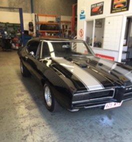 classic muscle car in mechanics shop