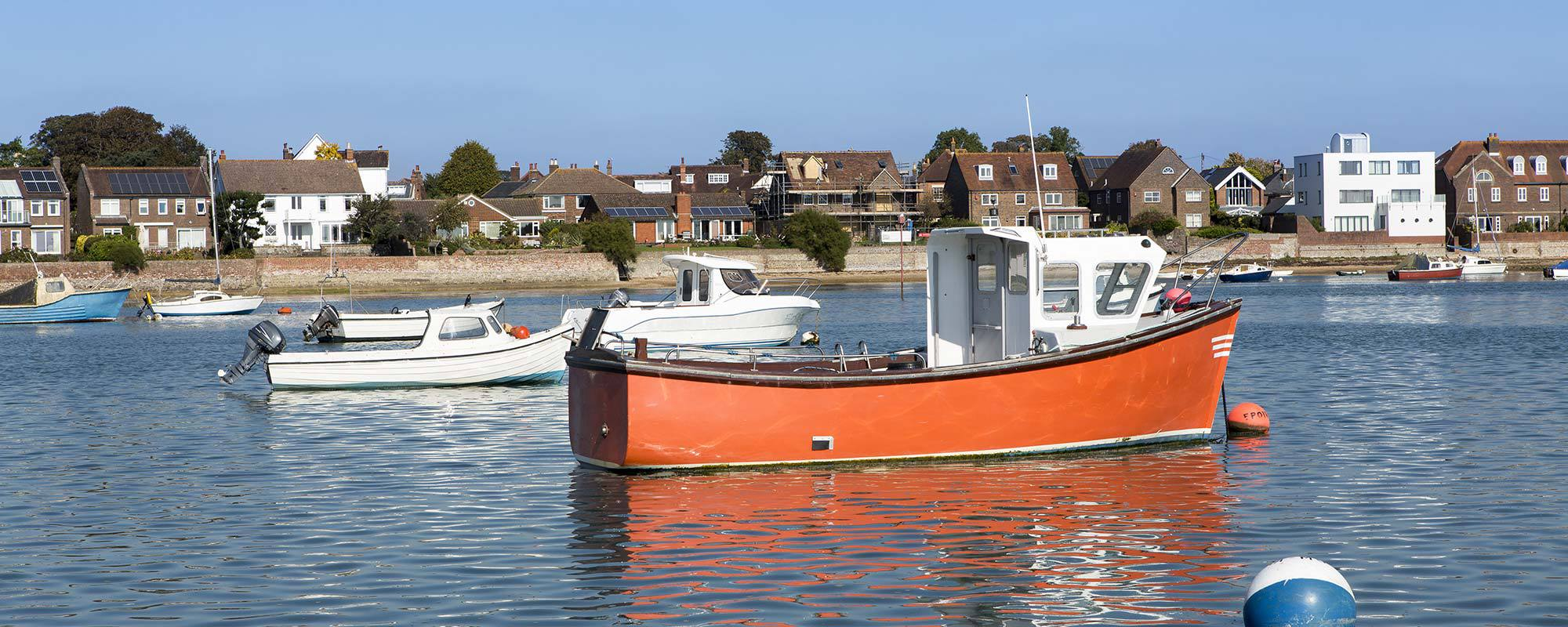 Red coloured fishing boat standing in still water in Chichester