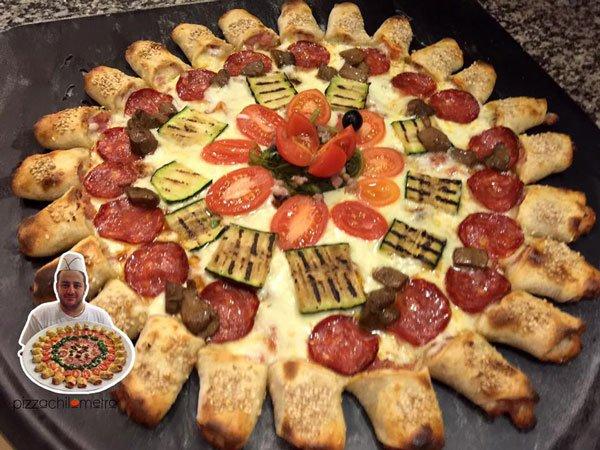 Una pizza a forma di  sole con raggi, farcita con salame, zucchine e pomodorini