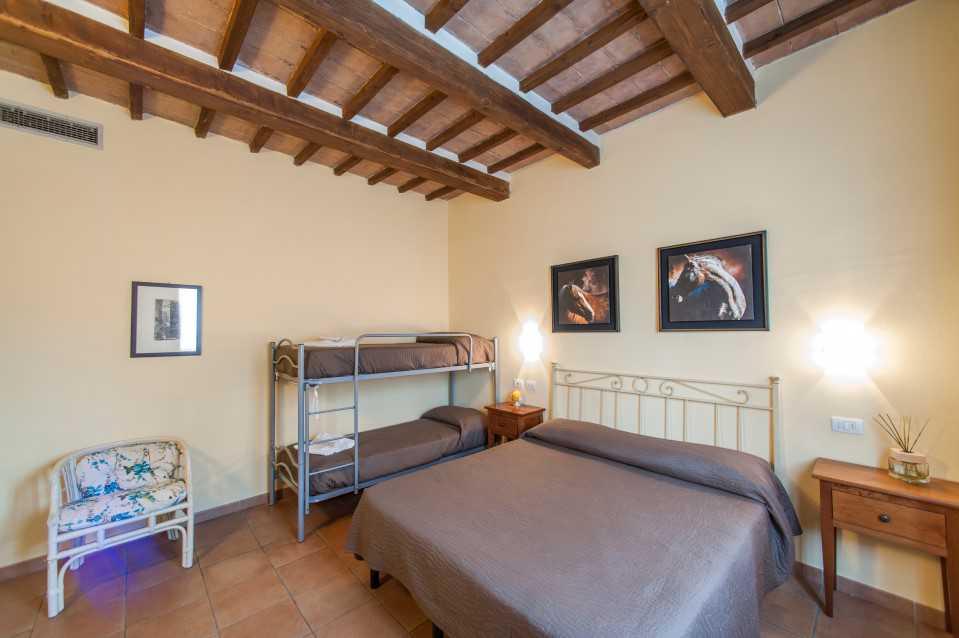 stanza con letto matrimoniale e letti a castello