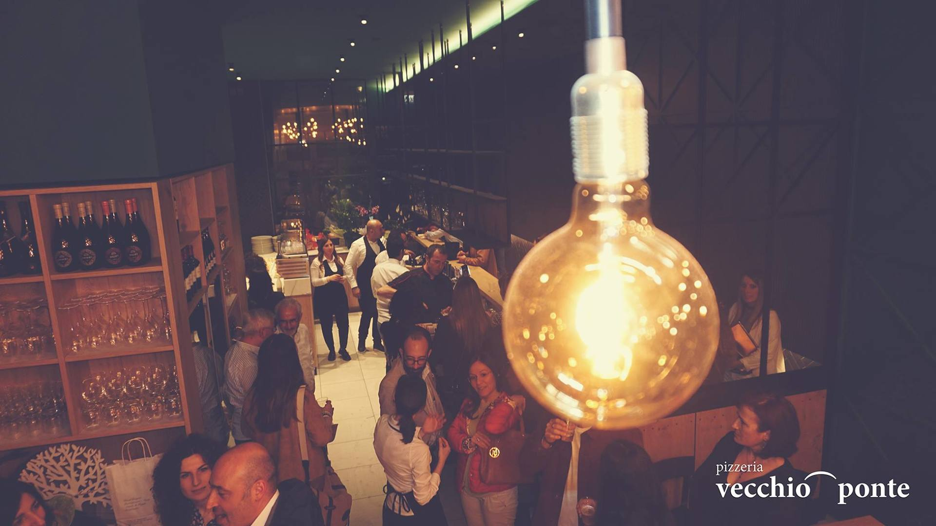 particolare lampada appesa con persone sullo sfondo