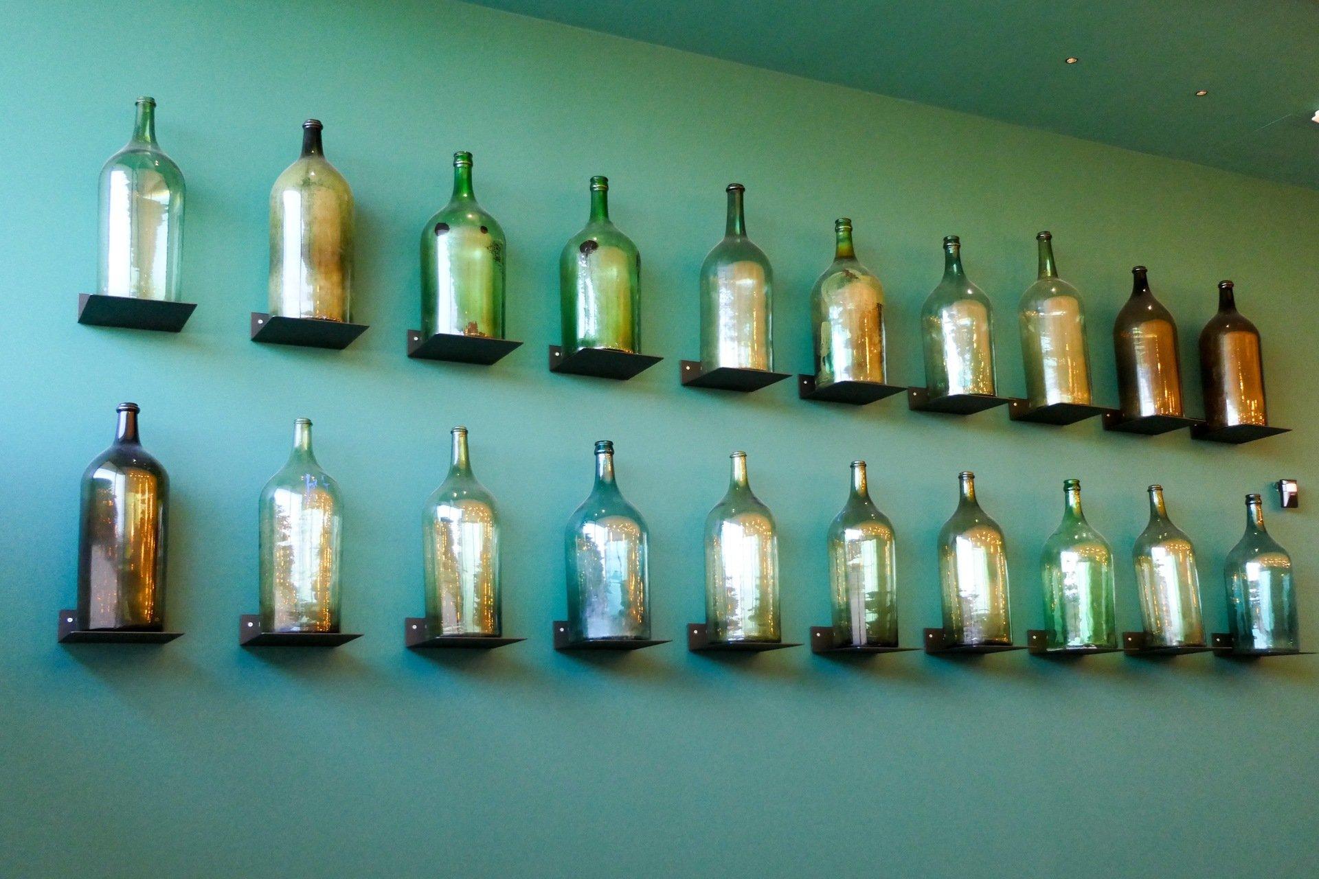bottiglie appese a muro verde