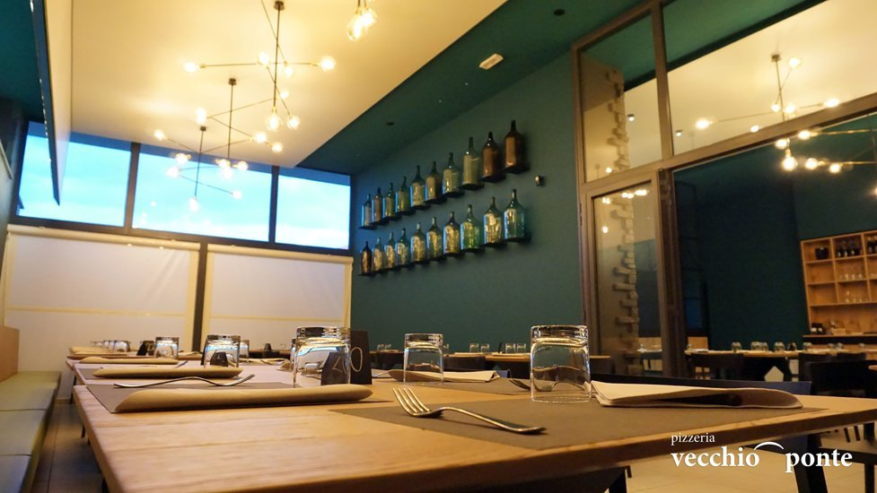 sala della pizzeria con assortimento di vini sulla parete