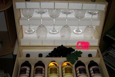 Confezione con bottiglie e calici da vino.