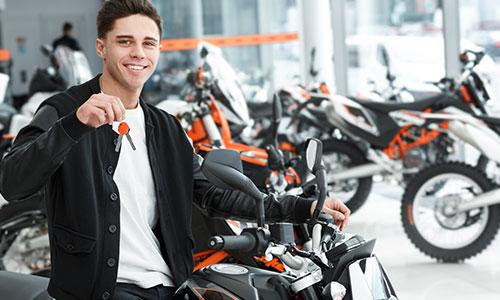 Ragazzo sorridente su una moto, chiavi in mano