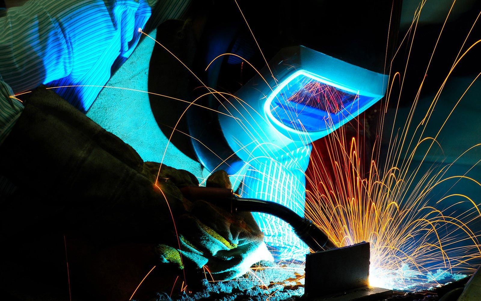 lavoratore che taglia ferro