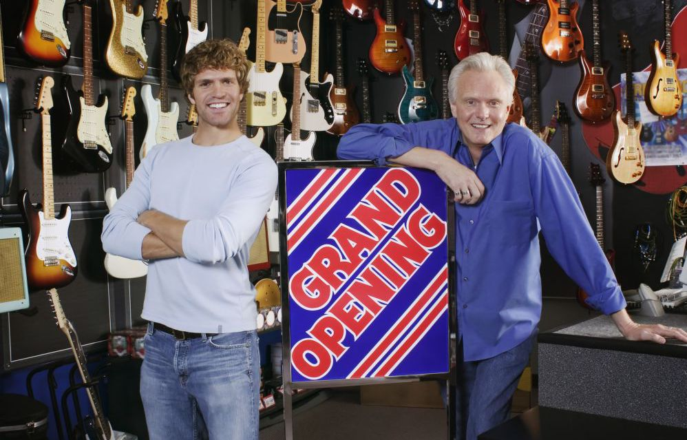 Business owners with grand opening signage in Jamestown, NC