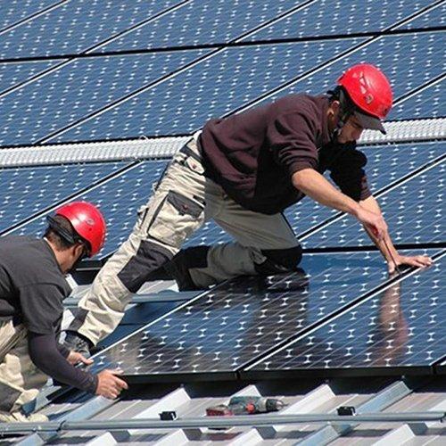 Operai installano pannelli fotovoltaici su un tetto