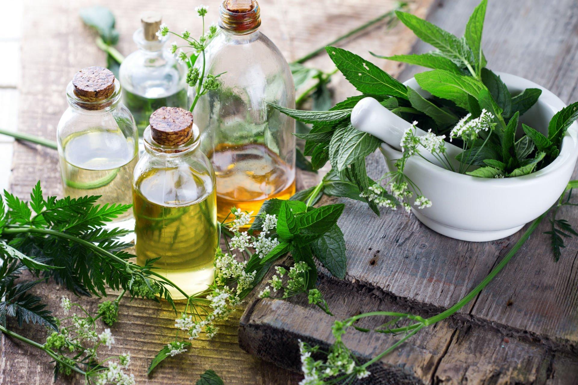 oli essenziali, erbe aromatiche e un mortaio di marmo