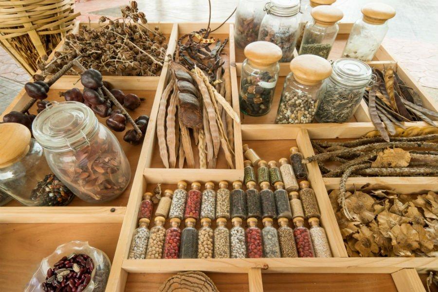 vassoio espositivo in legno con fiori essiccati, vasetti di spezie, erbe e semi