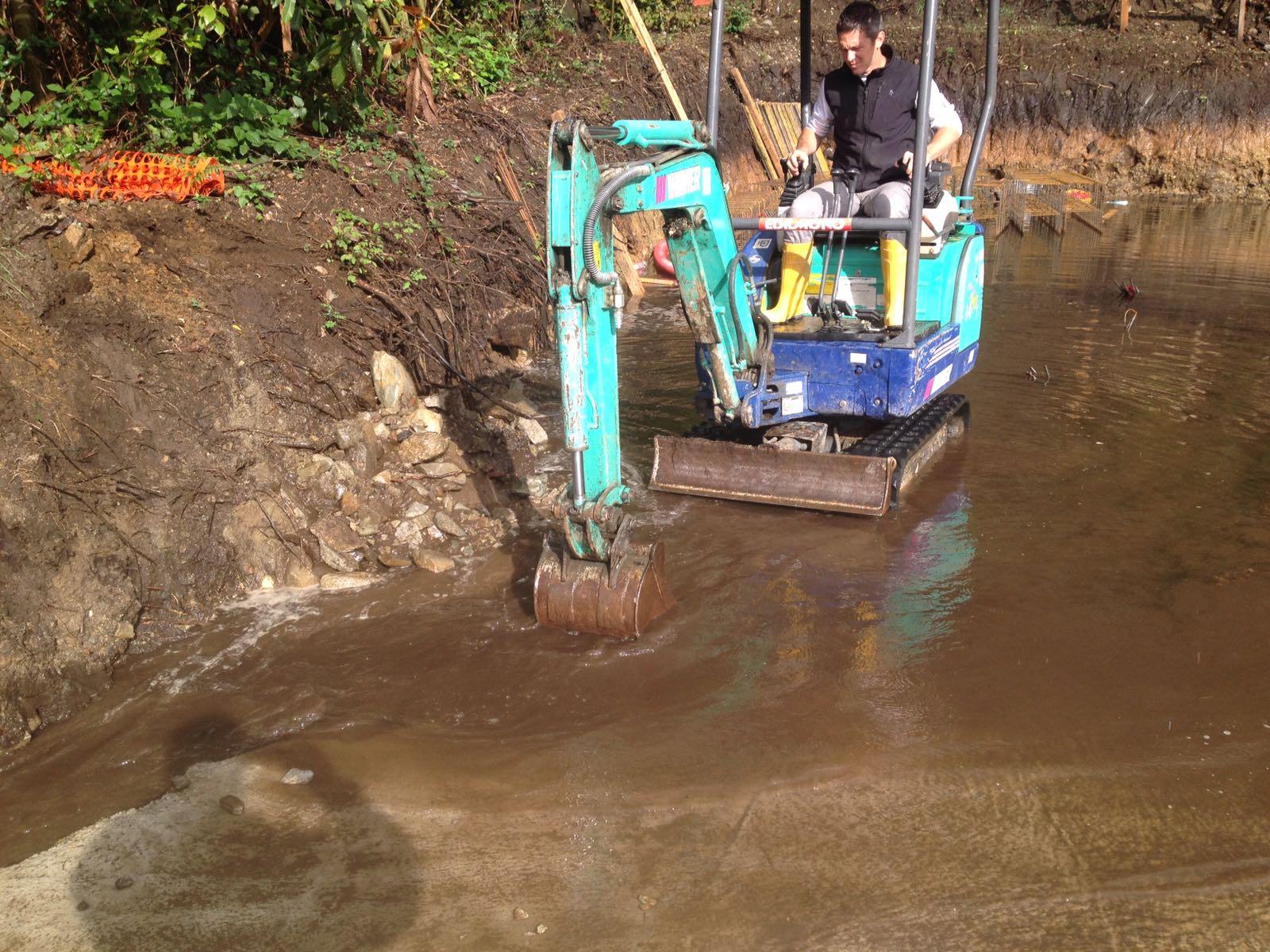 scavatorino che toglie acqua e terra da un sito
