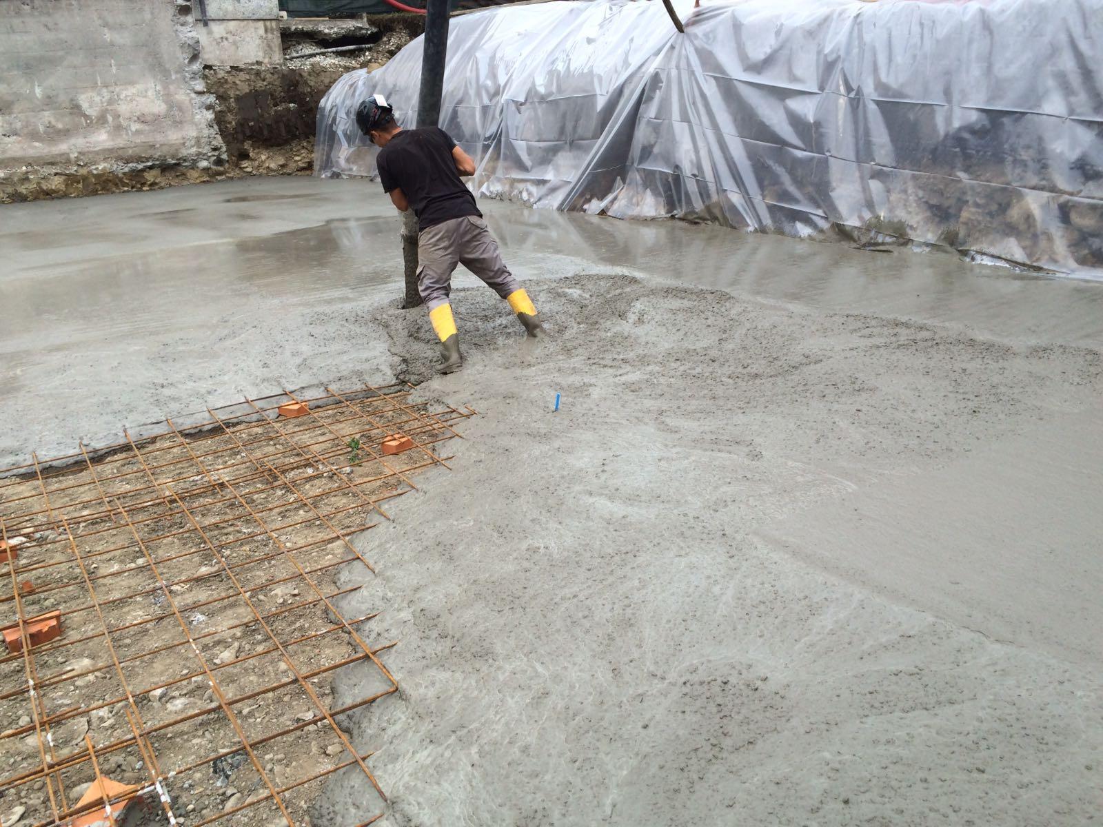 cemento gettato fresco con uomo che regge un palo