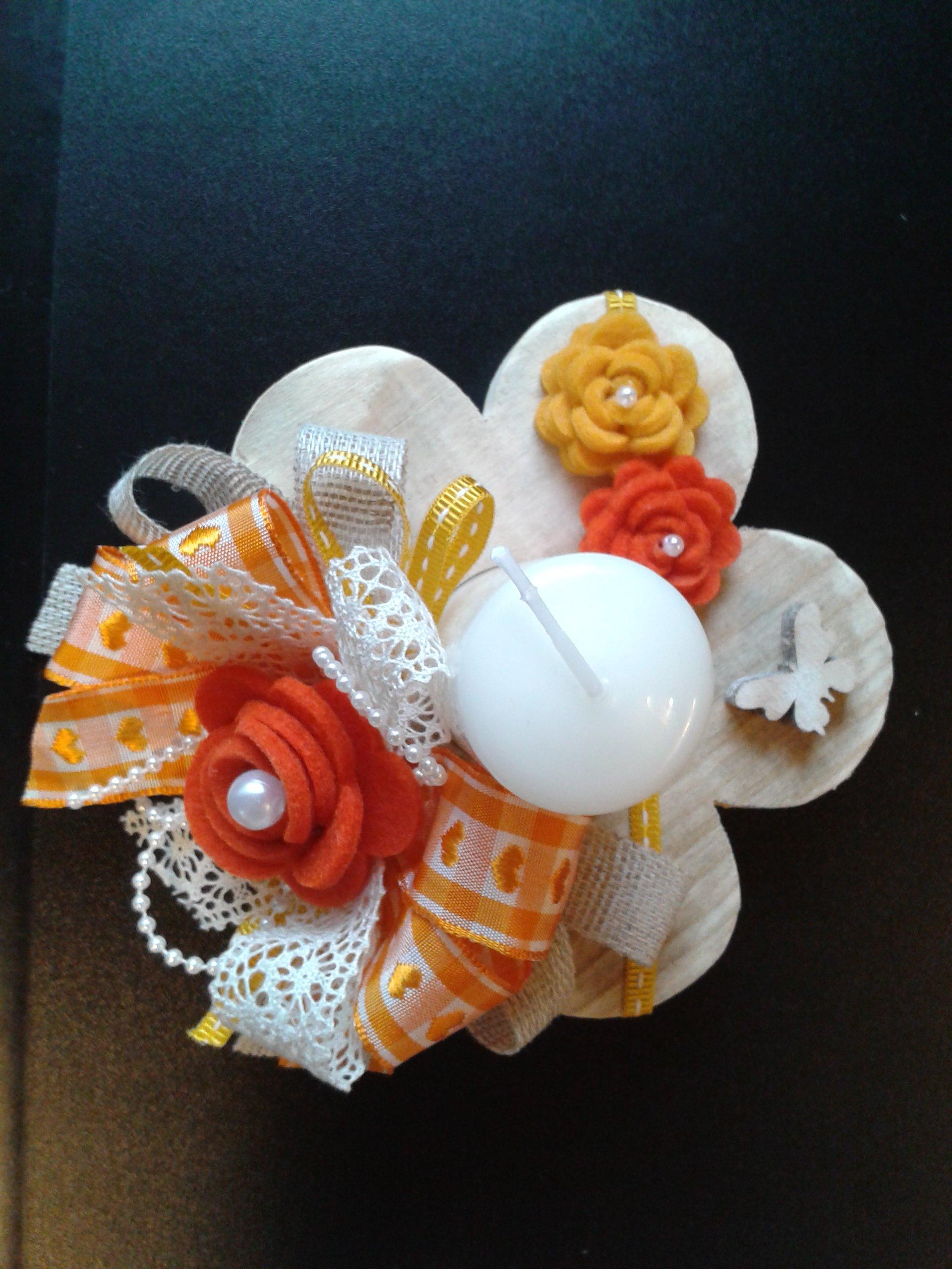 candela su un fiore di legno e fiochi arancioni e bainchi