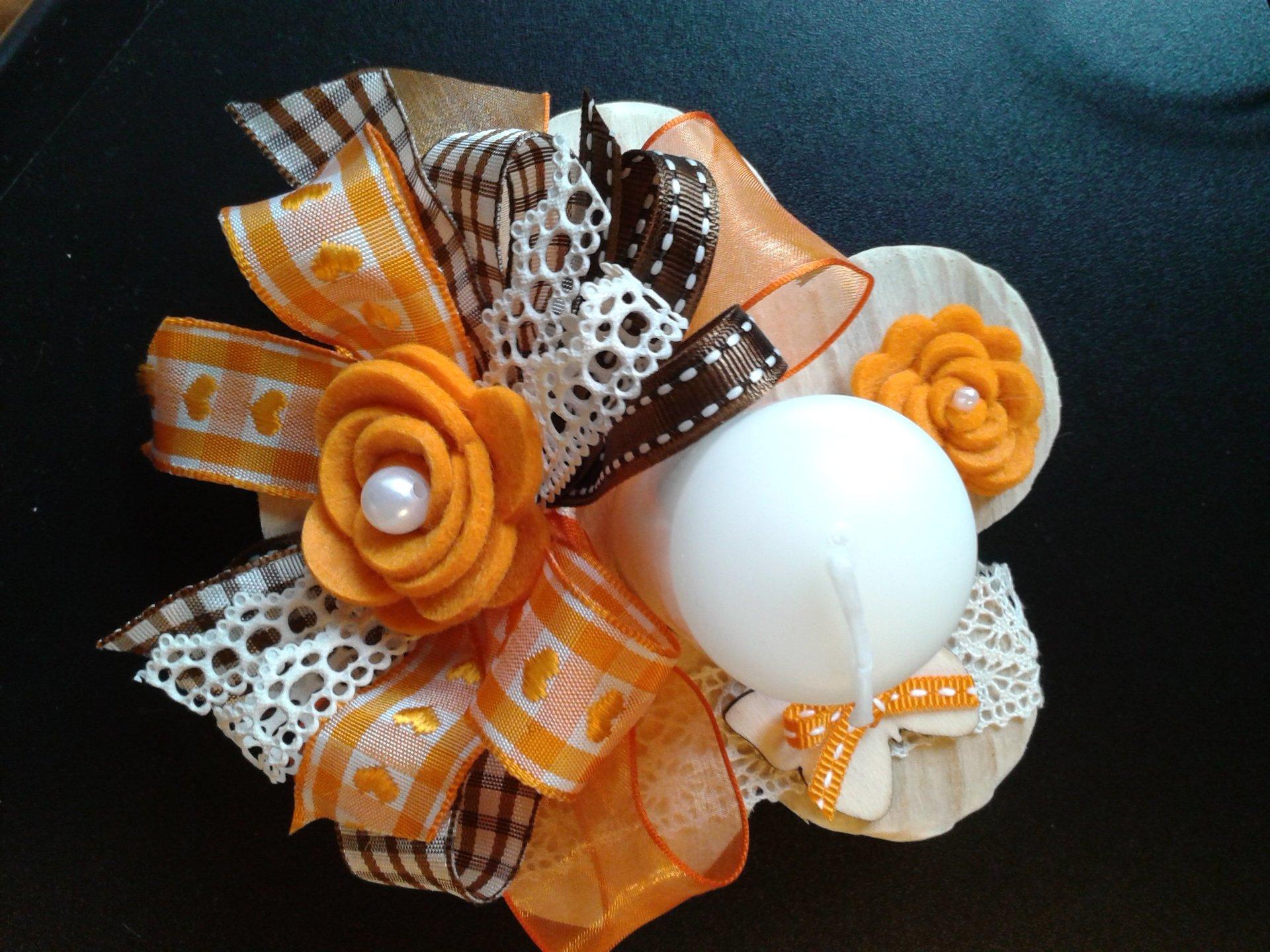 candela bianca circondata da fiore arancione in stoffa e fiocchi bianchi, arancio e neri