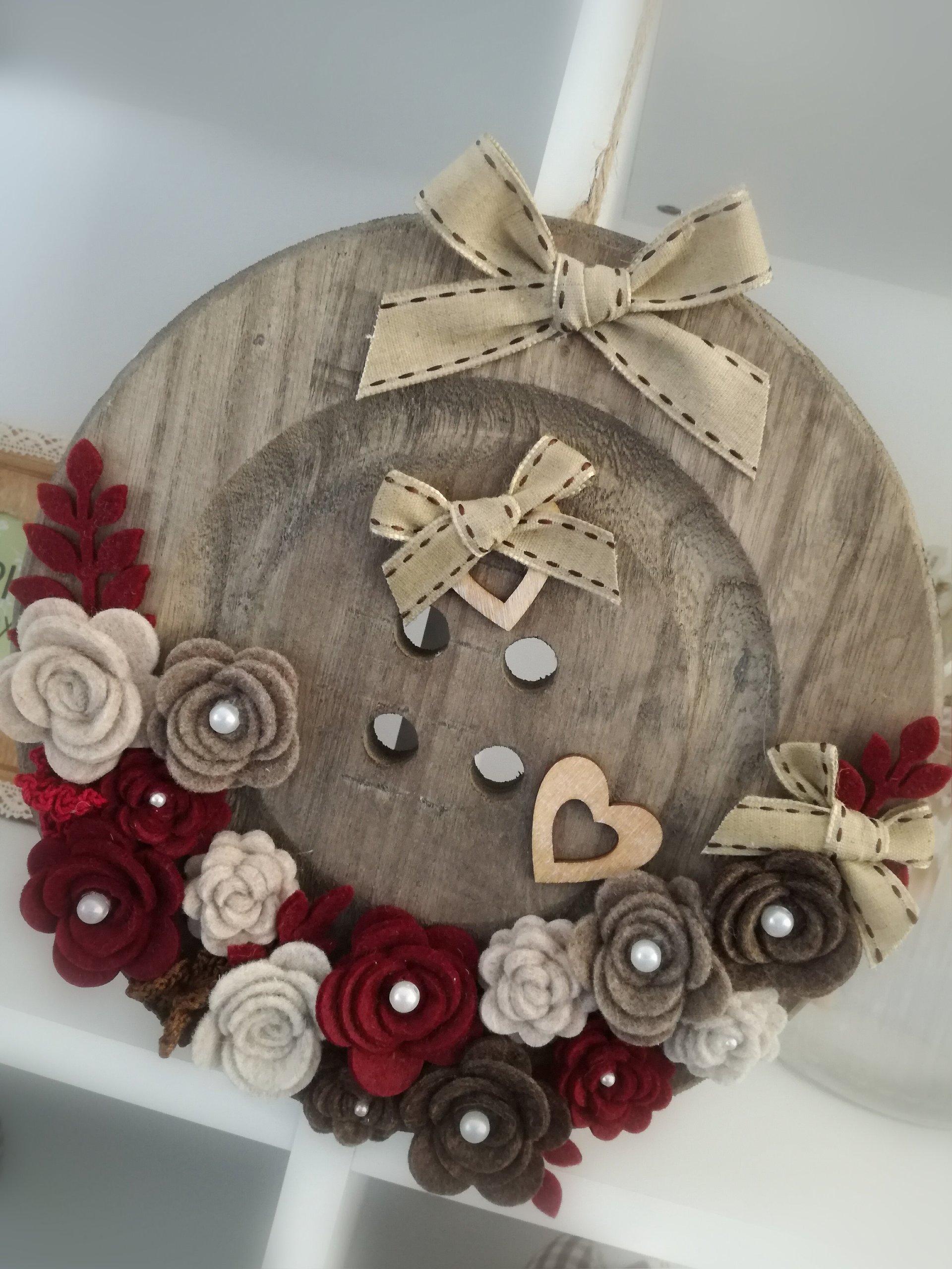 ghirlanda in legno con inserti di fiori rossi e cuoricini
