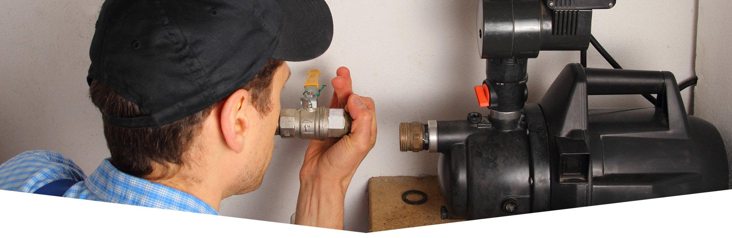 Un uomo effettua una manutenzione su un impianto idraulico