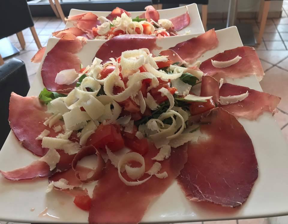 Piatto di prosciutto di Parma, con insalata di rucola e pomodoro con laminazione di formaggio parmigiano