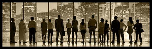 delle persone in piedi in un ufficio con delle vetrate e vista dei palazzi