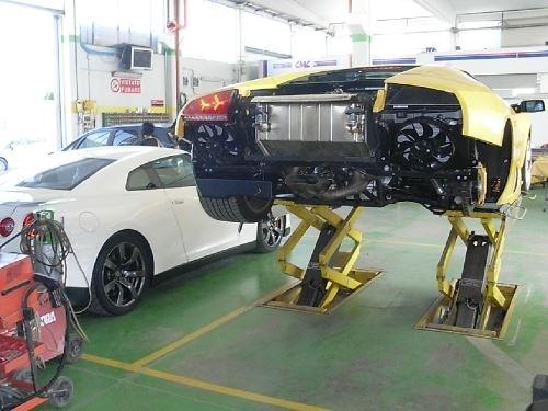 una macchina sportiva gialla in riparazione