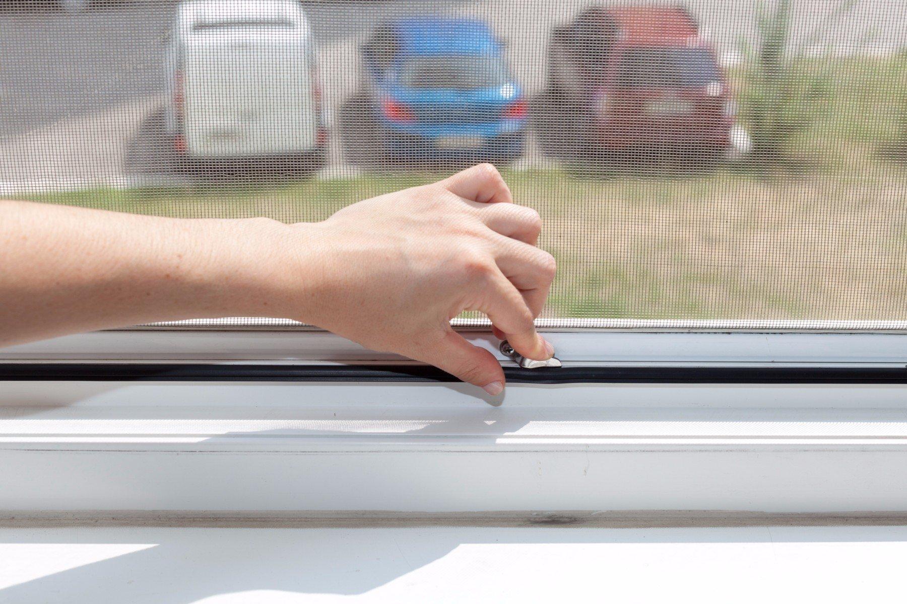 una mano che chiude una zanzariera di una finestra