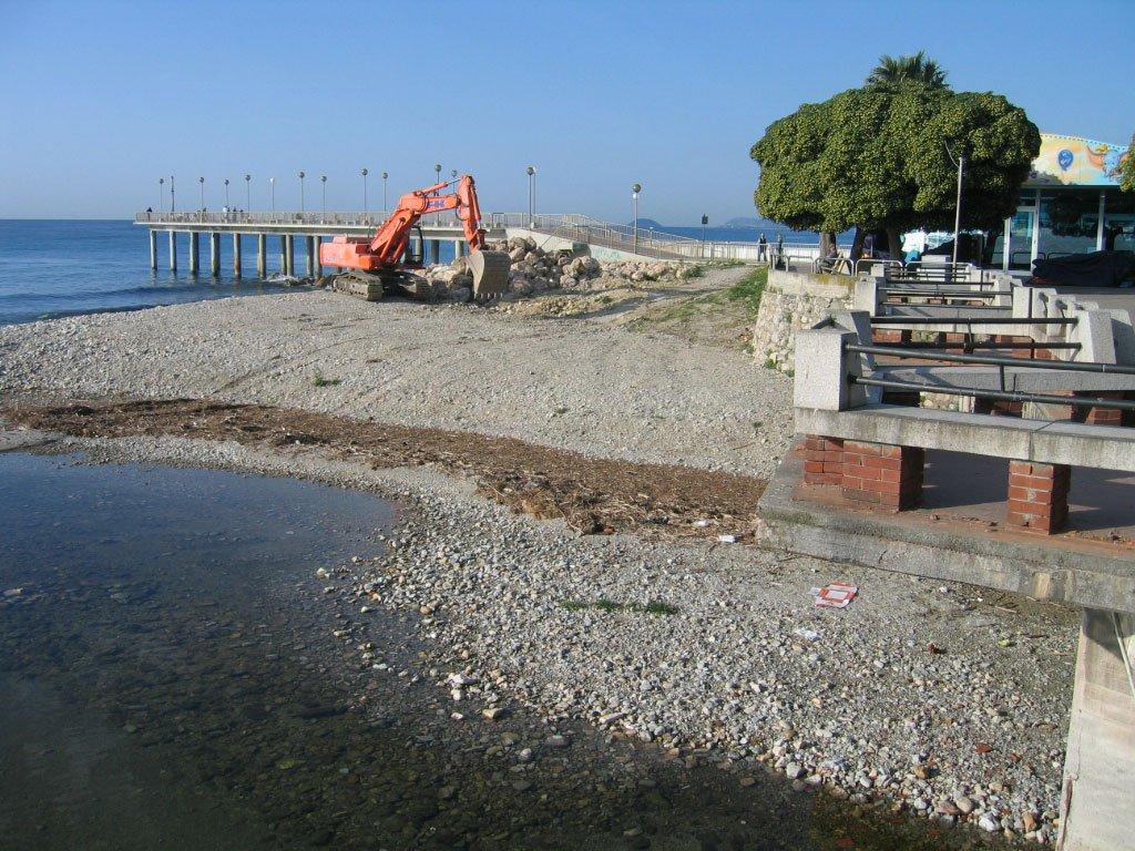 riva di un lago con uno ruspa rossa che sta scavando