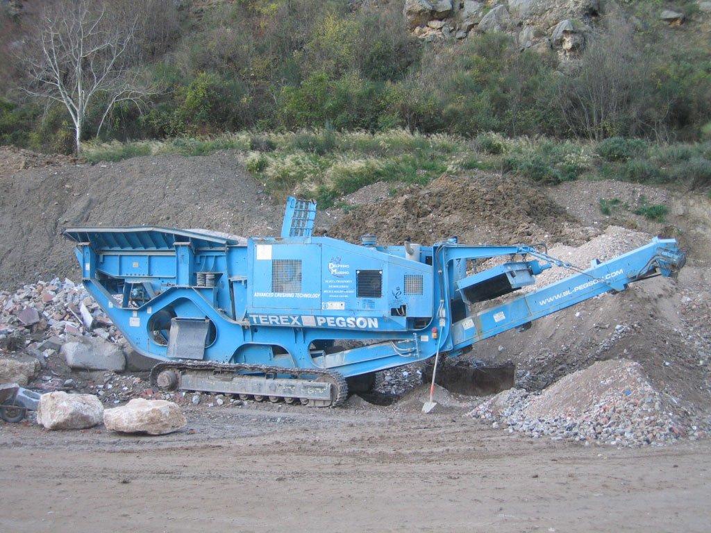 mezzo da lavoro cingolato di color azzurro vicino ad un cantiere in montagna