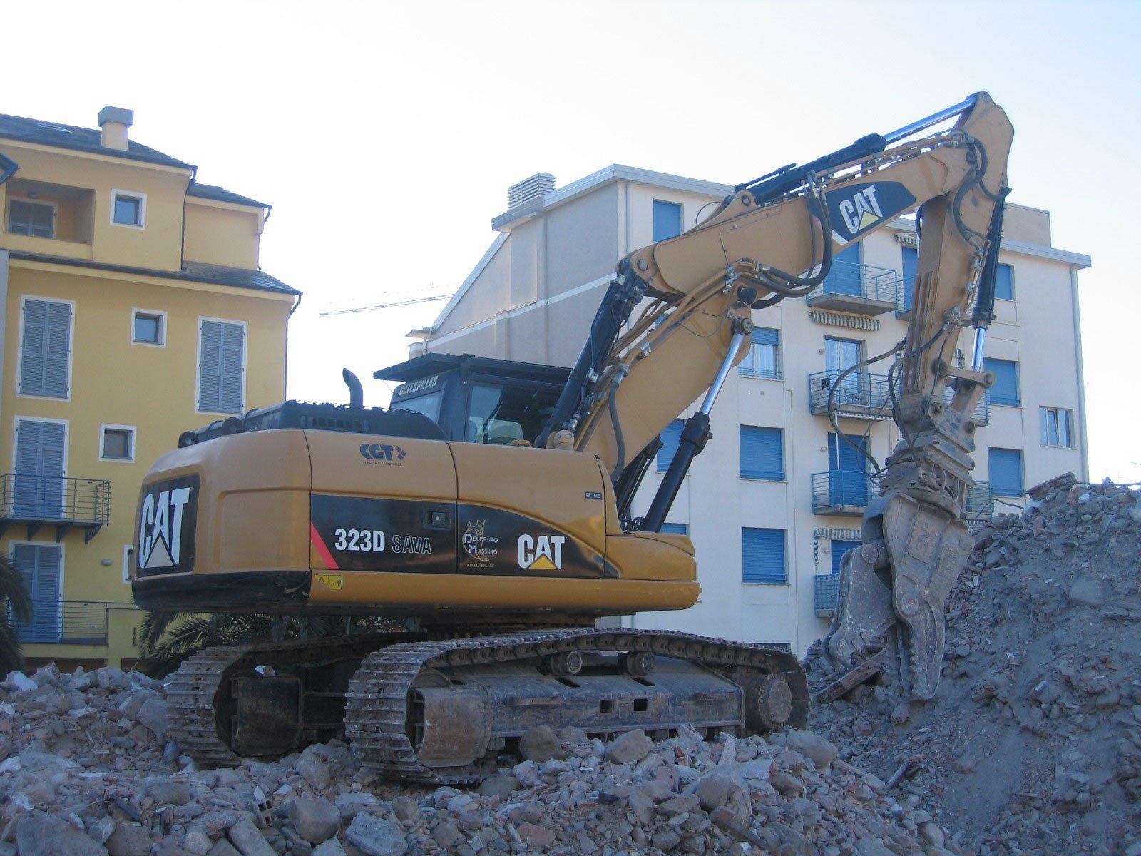mezzo da lavoro cingolato di color giallo sta scavando vicino a un condominio