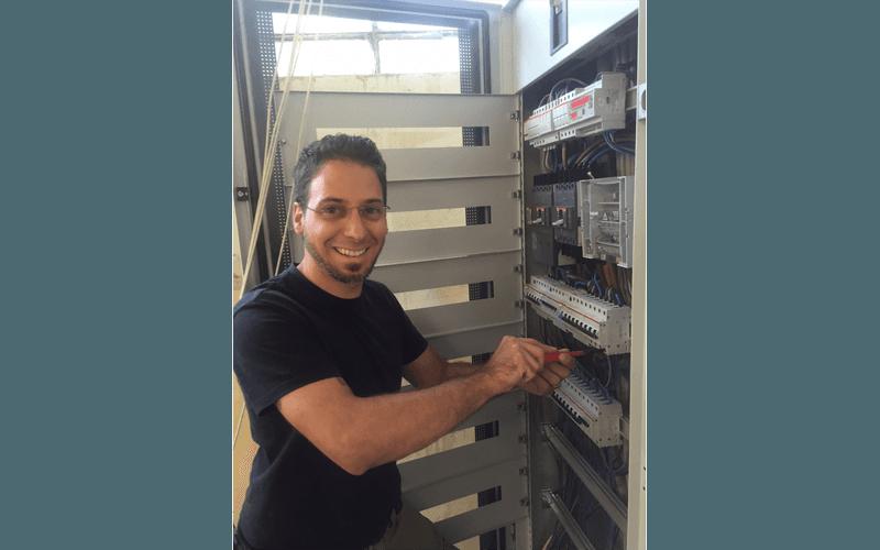 addetto sorridente durante un lavoro in una centralina elettrica