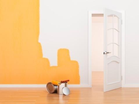 muro colorato di bianco e giallo con una porta aperta