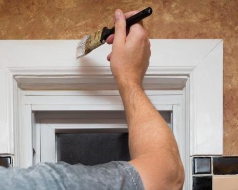 mano di un uomo mentre dipinge l`estermita di una porta