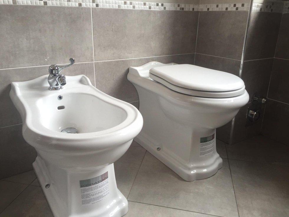 water e bide in un bagno con muro grigio