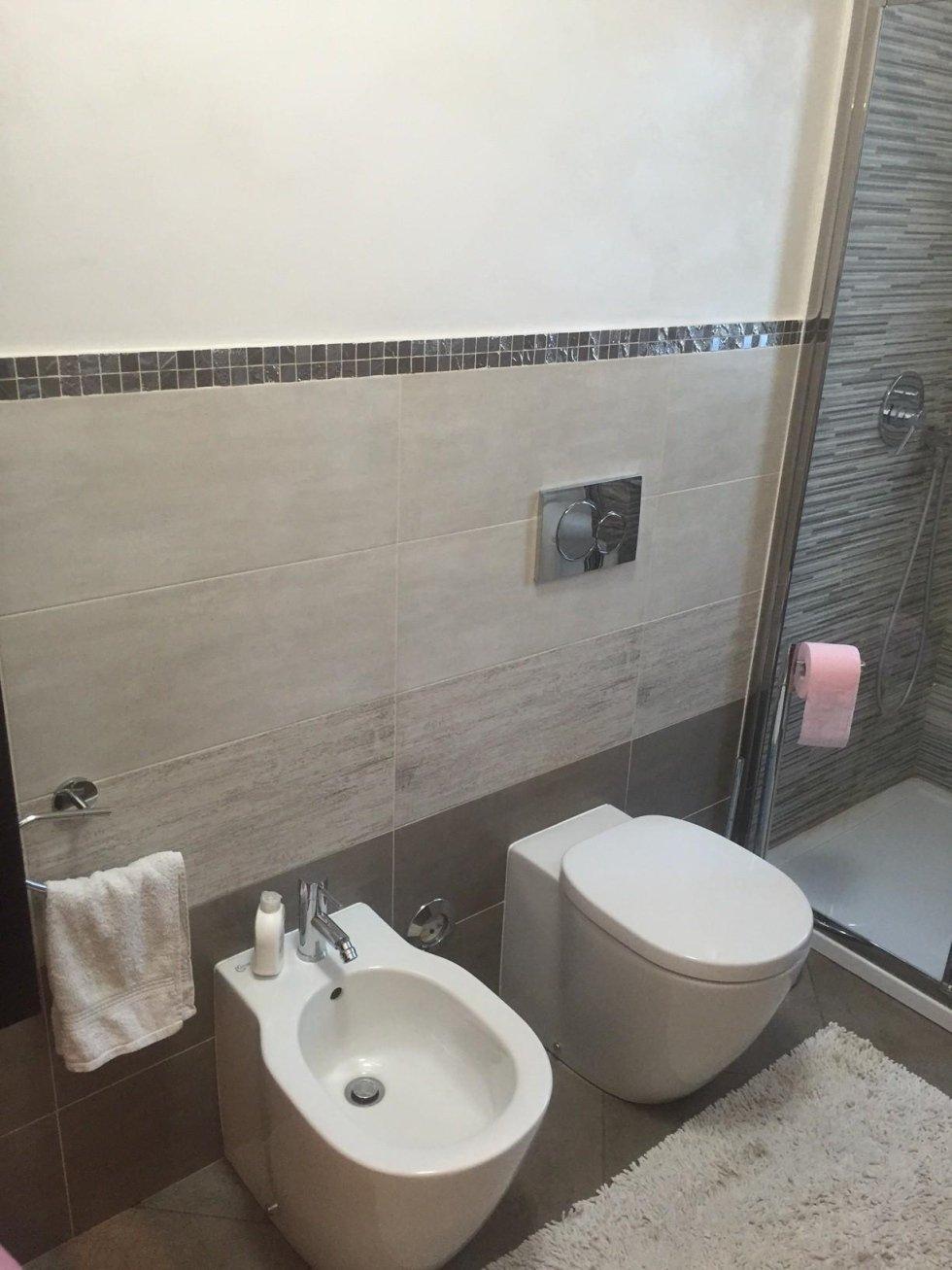 bagno con sanitari box doccia carta igienica e asciugamano vicino al bide