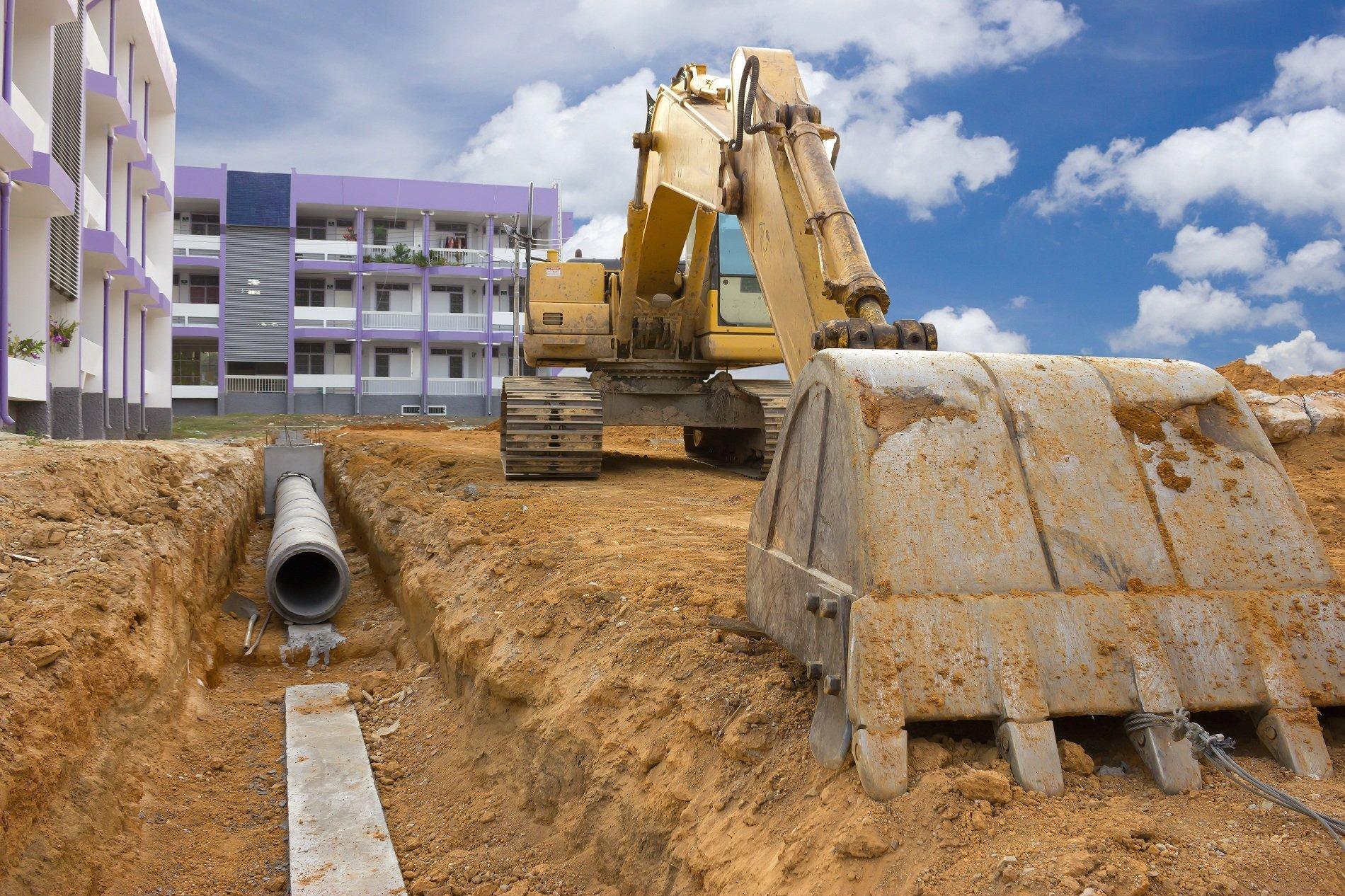 Escavatore sosta accanto a una trincea davanti a un edificio