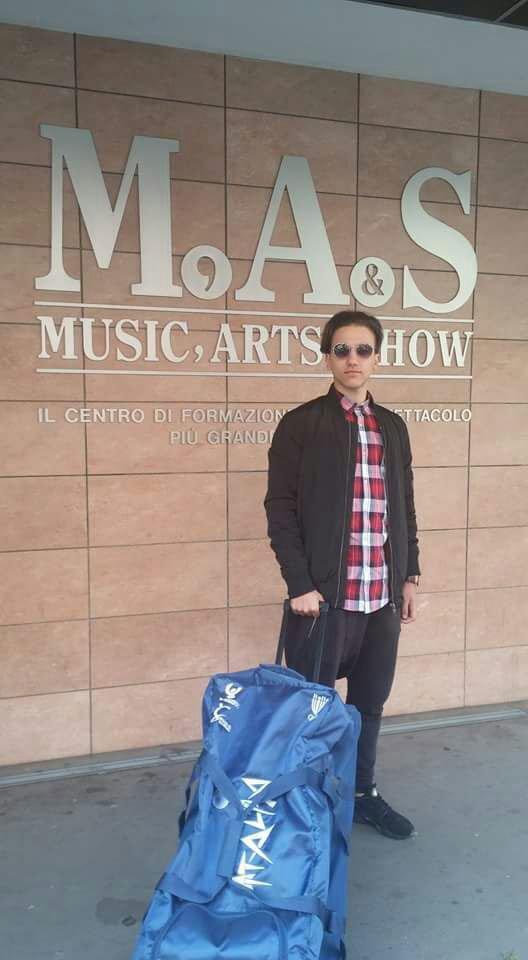 un ragazzo con un trolley e dietro la scritta M.A.S