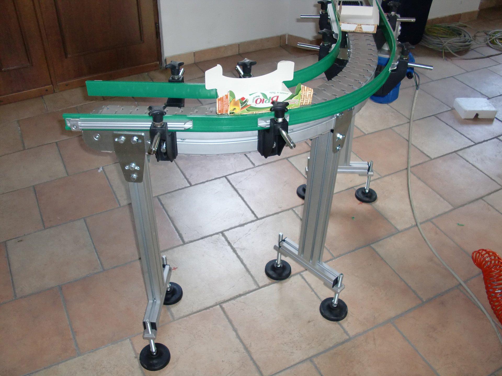 una struttura in ferro di color verde con dei rulli e sopra una scatola