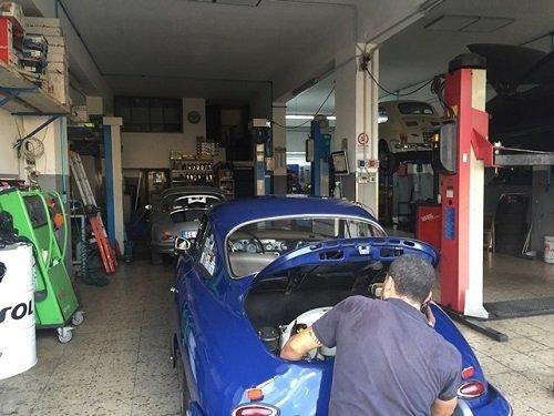 Meccanico ripara una macchina blu con il baule aperto