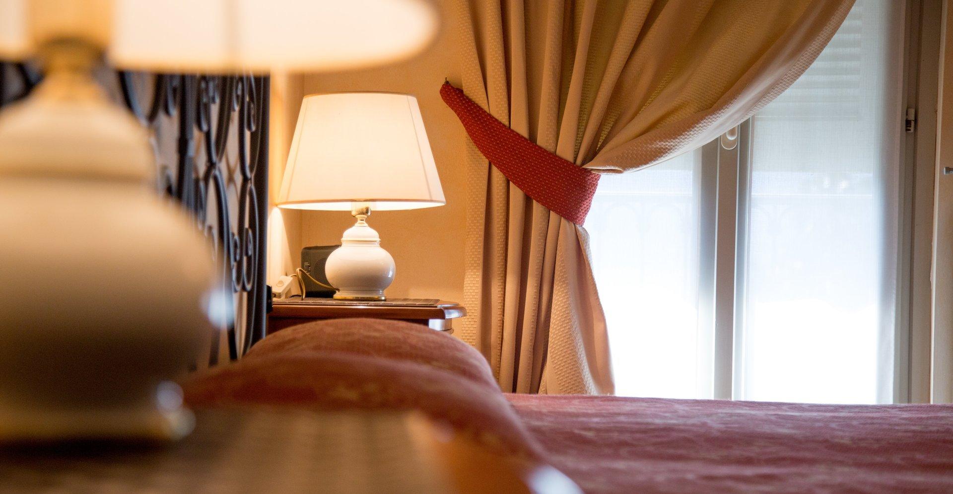 stanza di albergo, letto, tende e lampade
