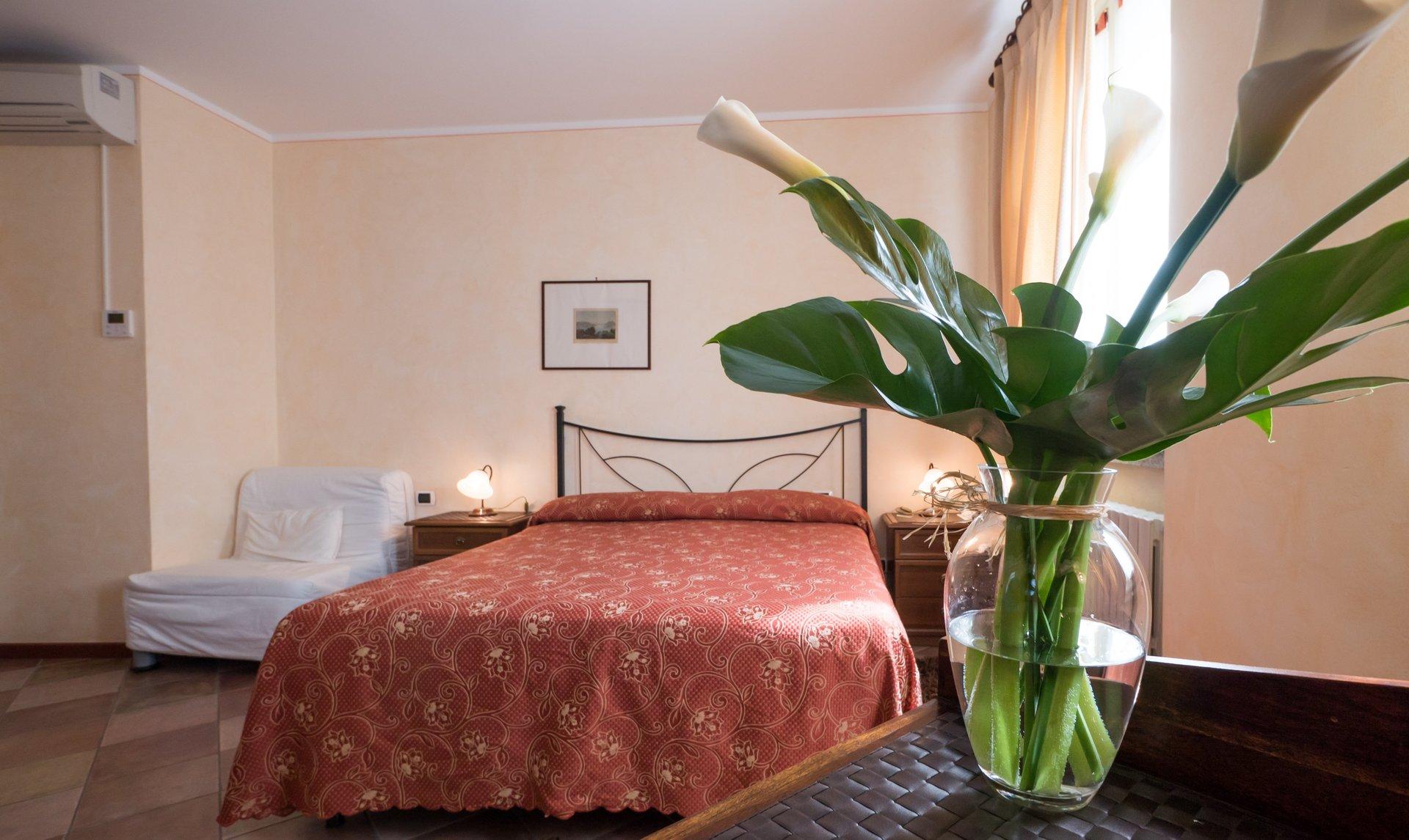 stanza di albergo con primo piano di vaso con fiori