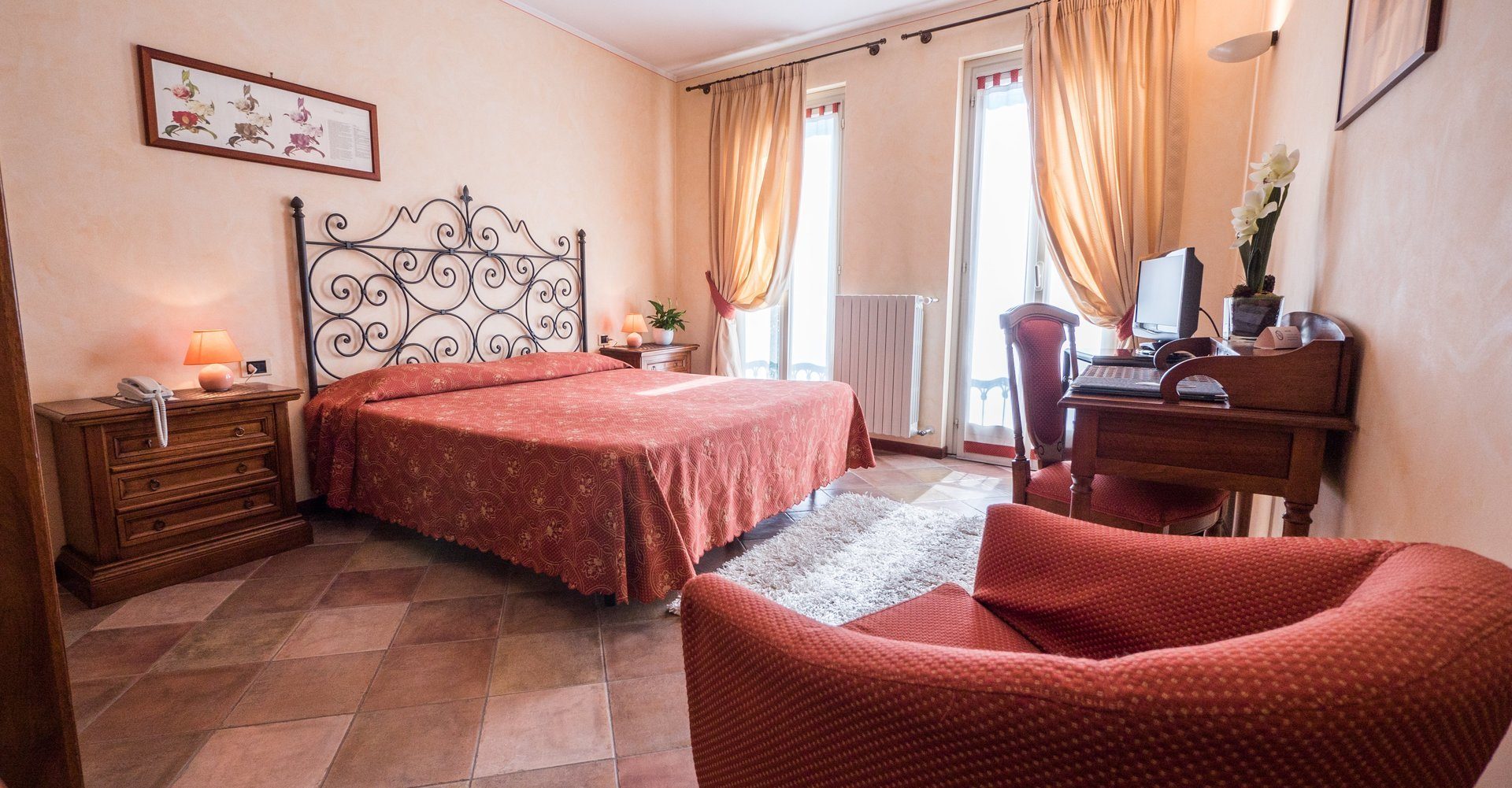 camera doppia con letto matrimoniale, poltrona e scrivania