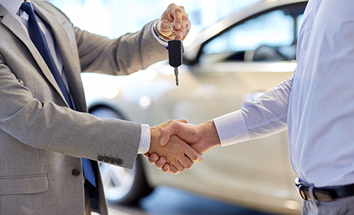 Dealer handing over the car keys of the second hand cars to a customer in Peterborough