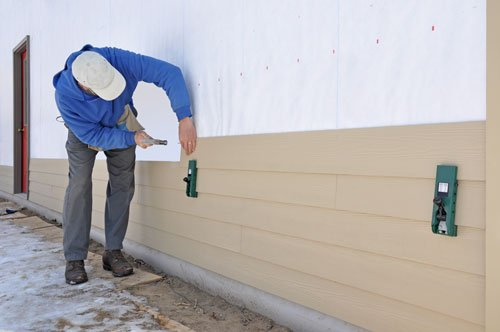 Man installing fibrous cement siding using siding gauges