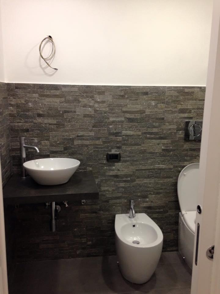 Bagno bianco ristrutturato con lavabo in pietra