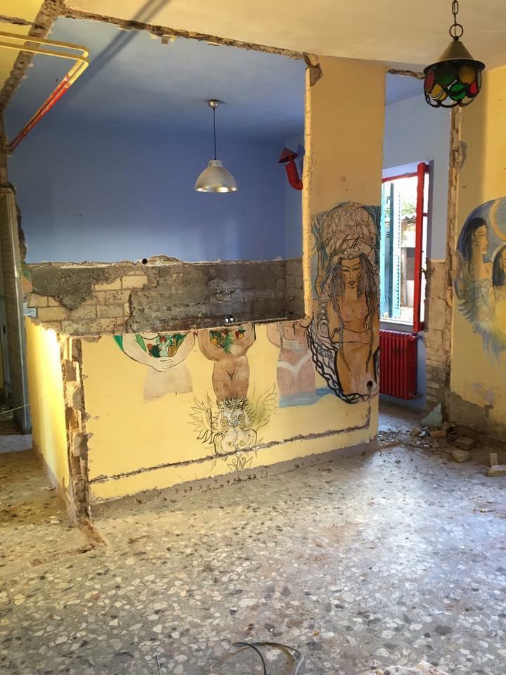 Stanza con parete gialla e disegni vari in fase di ristrutturazione