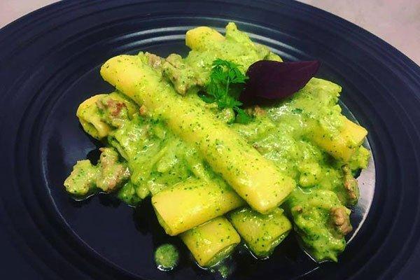 un piatto di pasta con una salsa gialla con erbe verdi