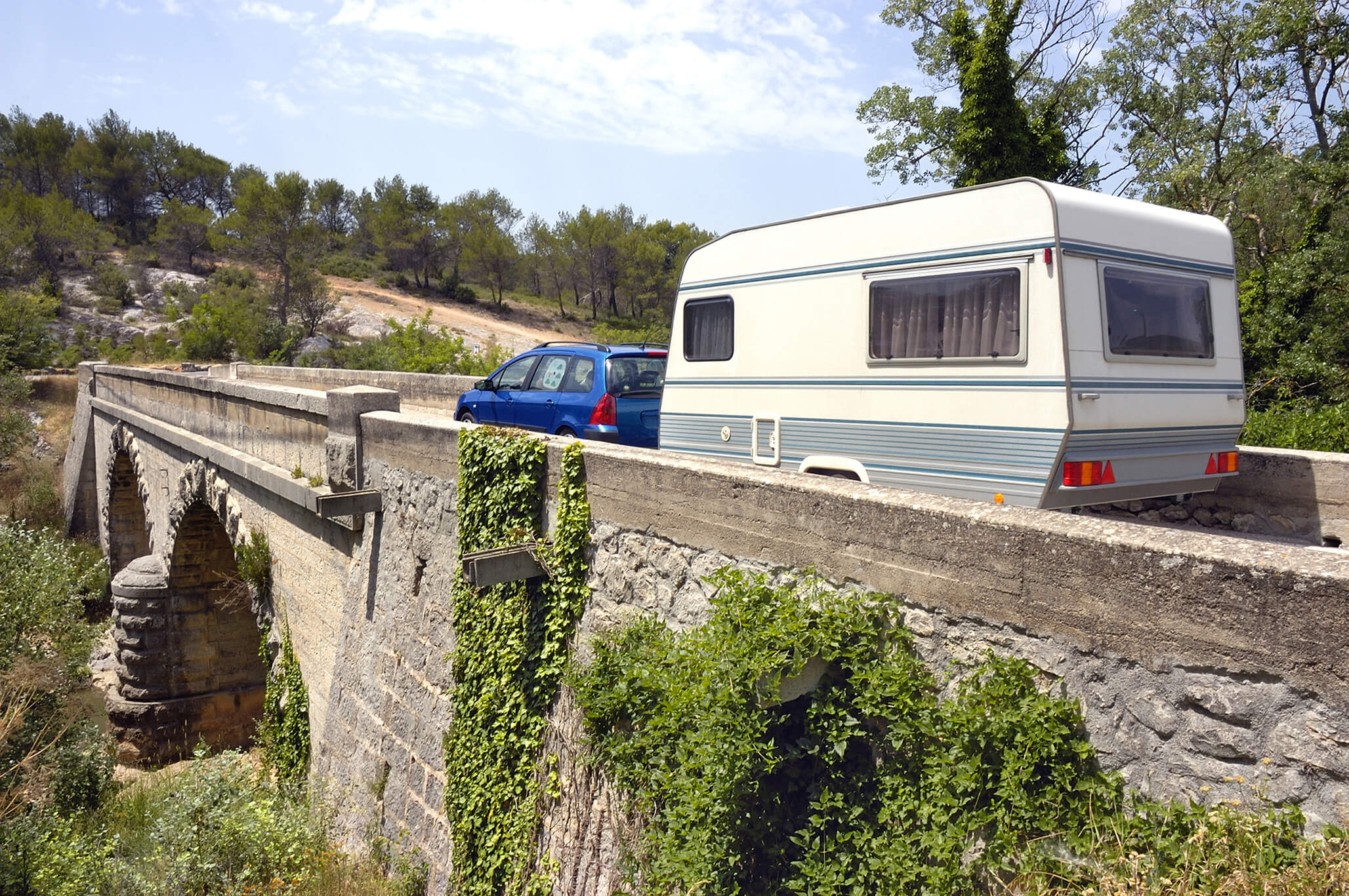 blue car with caravan on bridge