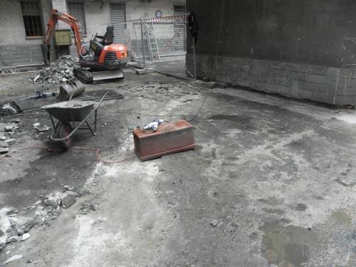 una carriola, e una scavatrice al lavoro sull'asfalto