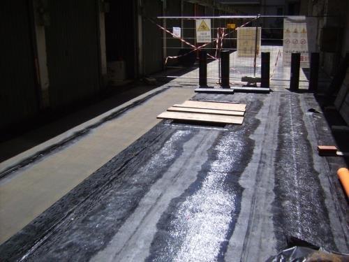 dell'asfalto bagnato e in fondo una rete metallica con dei cartelli di lavori in corso