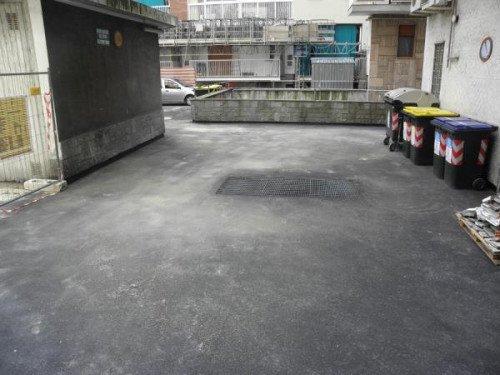 vista di uno spazio asfaltato e sulla destra dei cassonetti dell'immondizia
