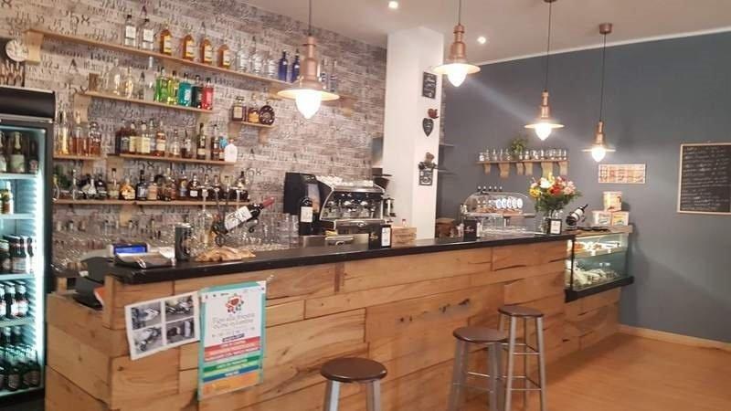 un bancone di un bar con vista delle mensole con delle bottiglie
