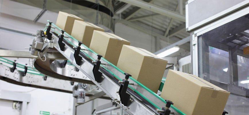 degli scatoloni su una struttura in pendenza in un'industria